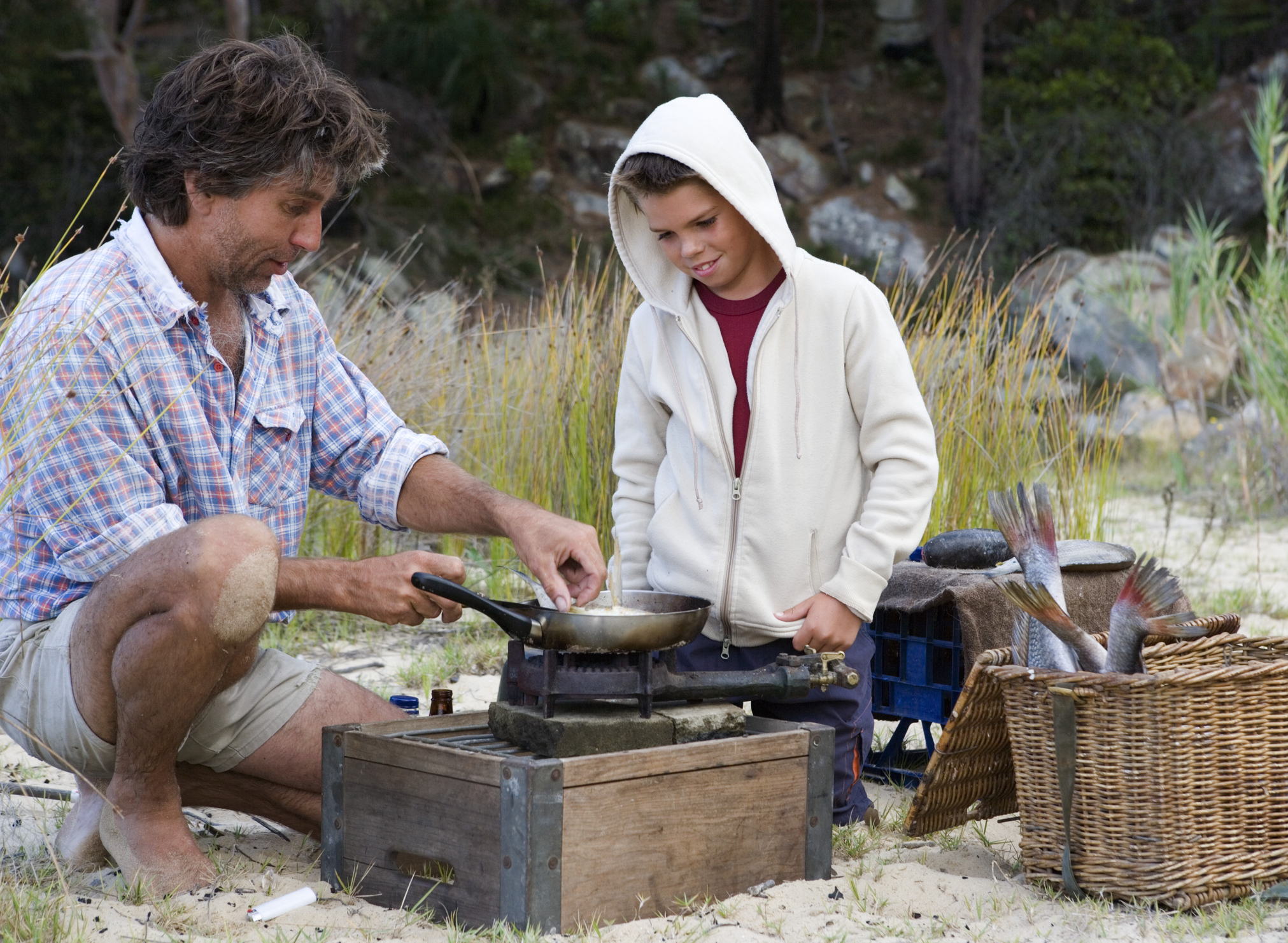 Dad teaching his son how to cook in the bush
