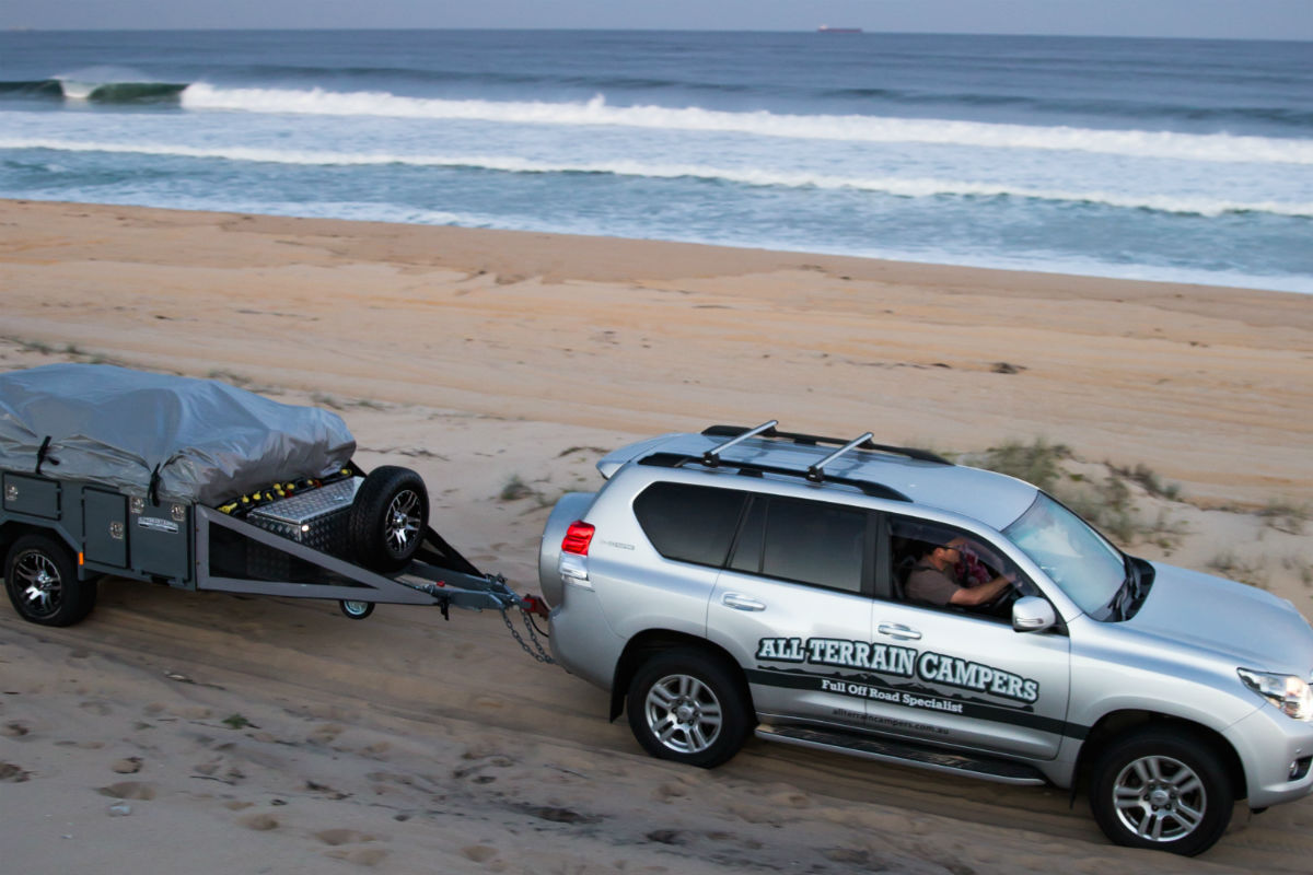 All terrains campers 4WD towing a trailer on the beach