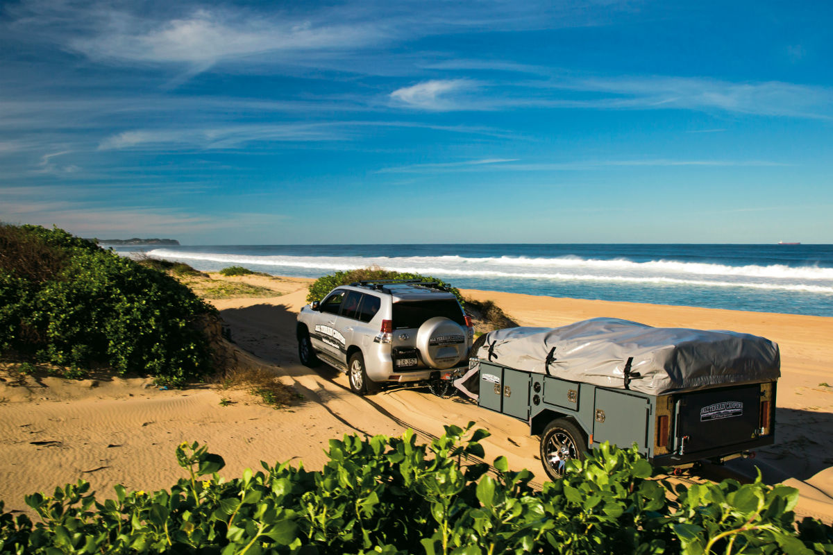 4WD towing a trailer on sand dunes near the beach
