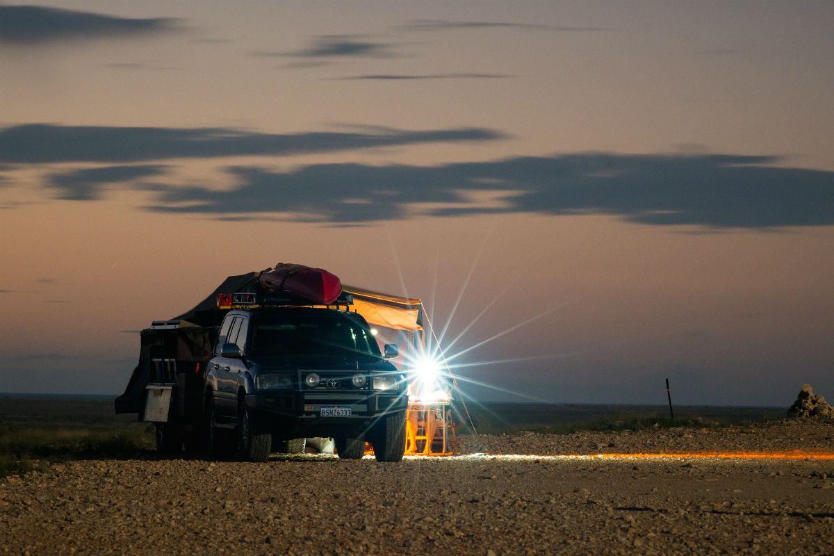 4WD parked in the desert during sunset with a flood light on