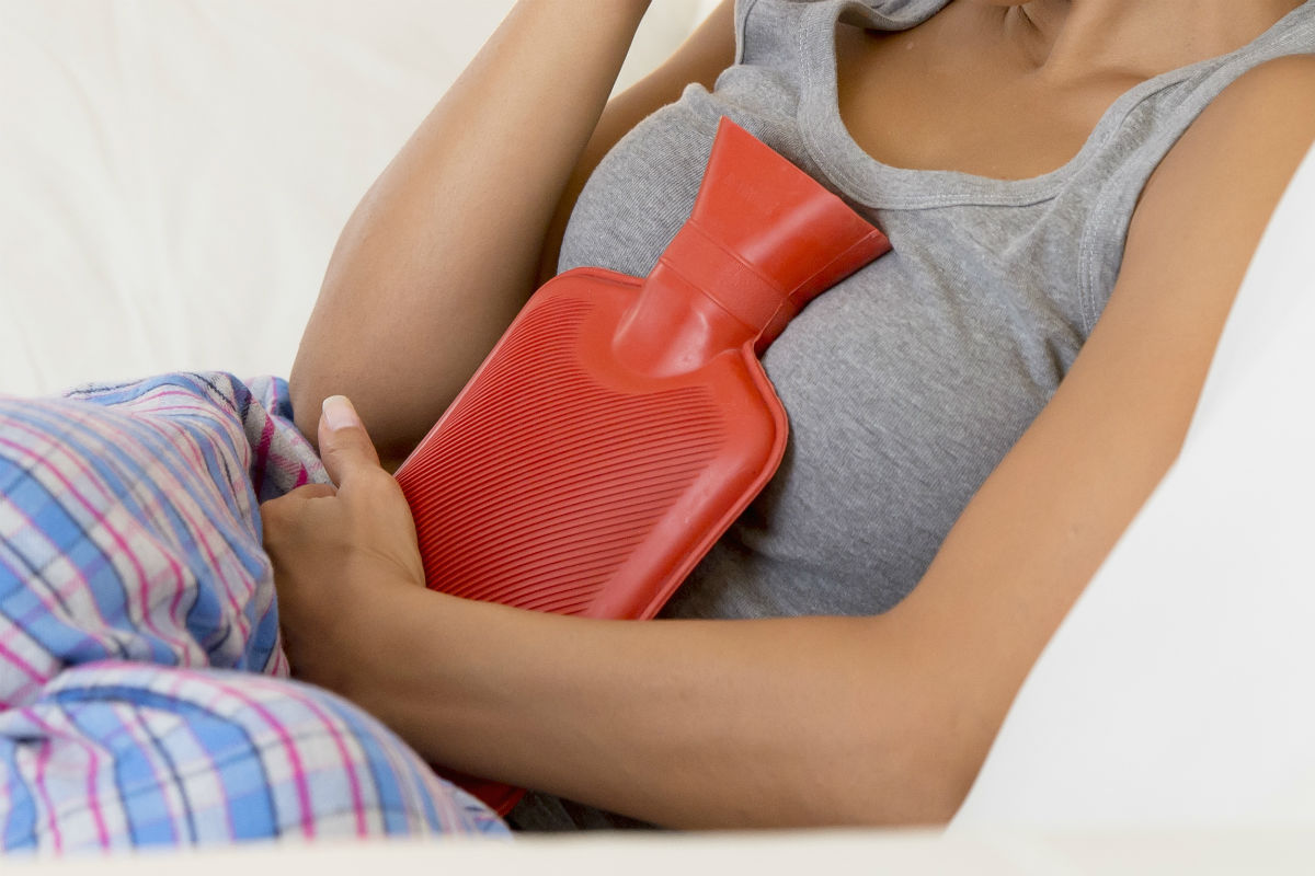 Woman holding a hot water bottle in her pyjamas