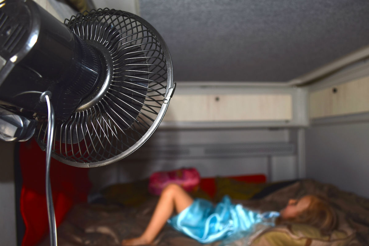 girl lying on caravan bed with the fan on