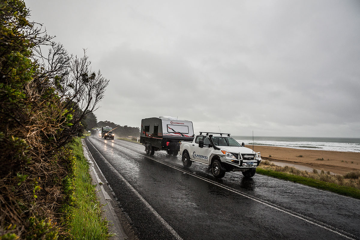4WD towing a caravan driving parallel to the beach on a wet day