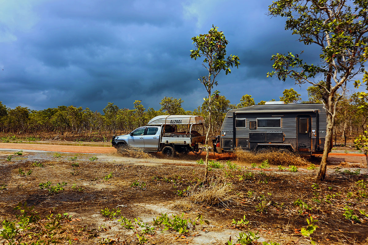 4WD towing a caravan on a country dirt road on a cloudly day