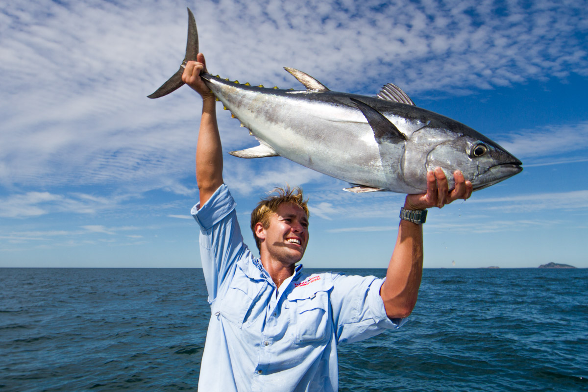 Man holding up a blue fin tuna on boat