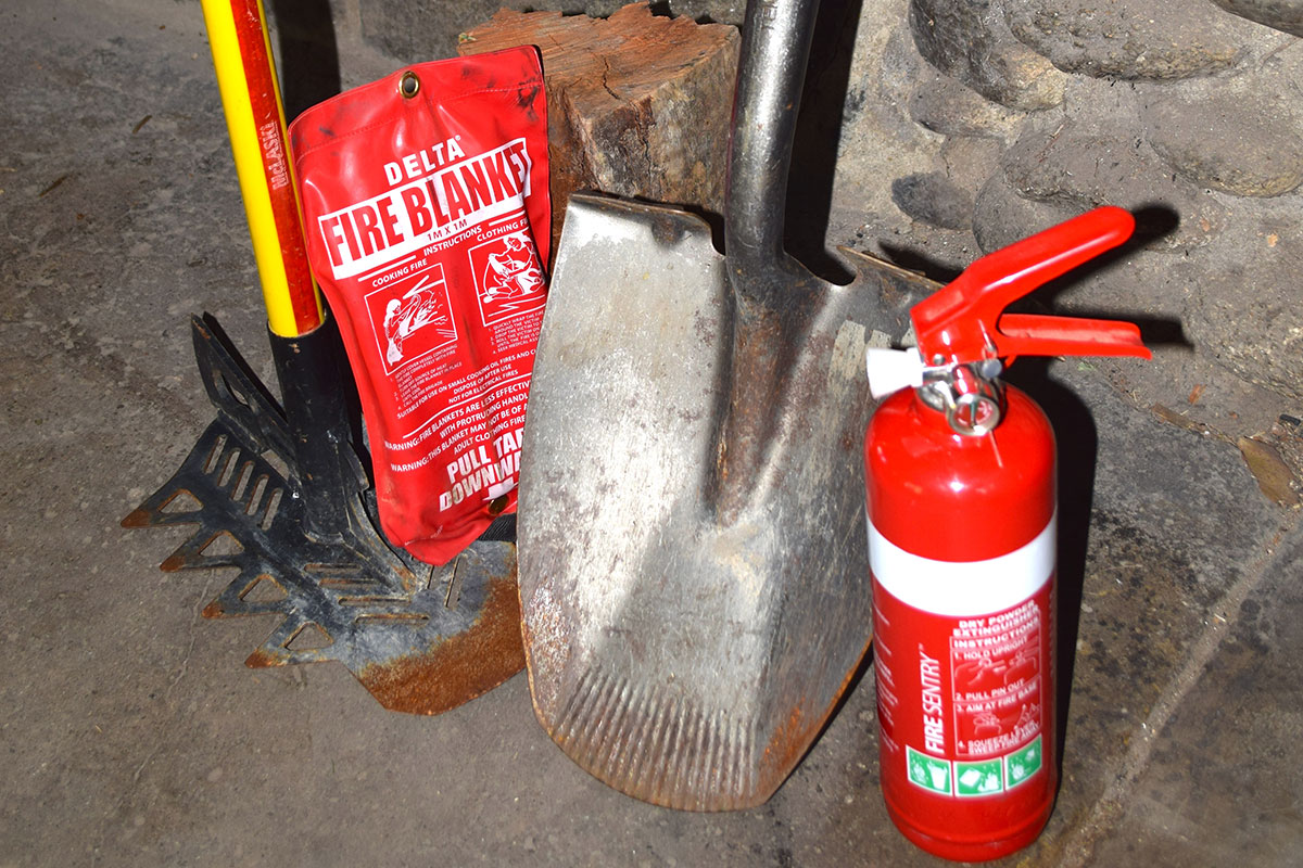 Fire saftey kit containing extinguisher, spade, fire blanket and rake