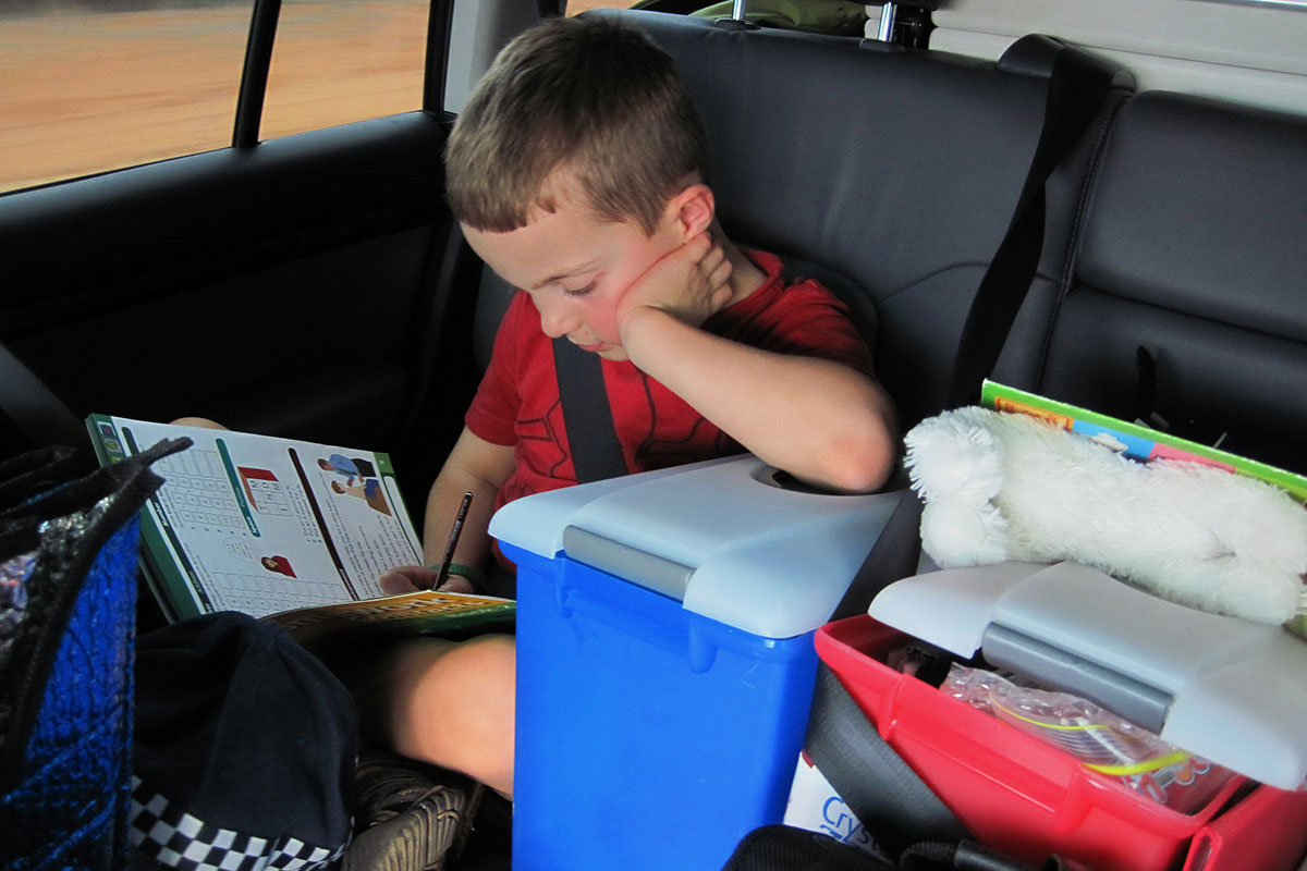 boy doing activities in the back of the car
