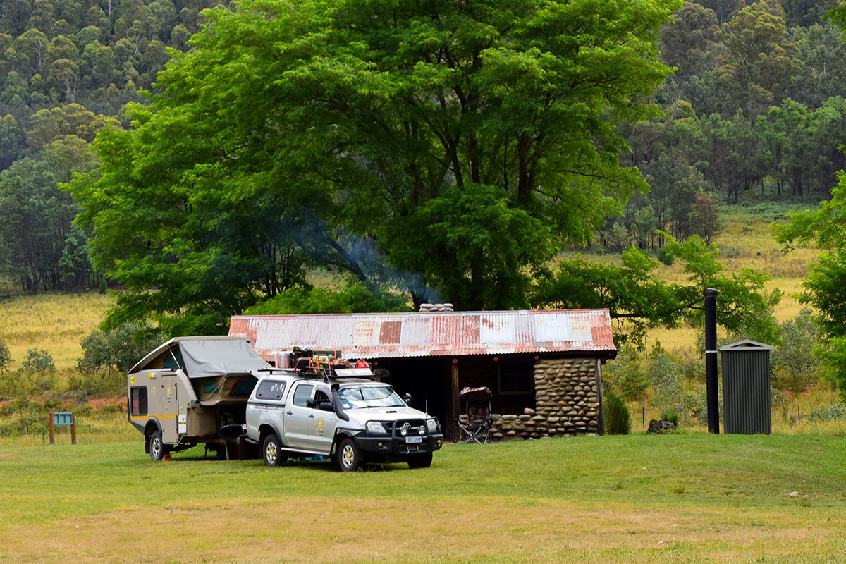 4WD towing a camper trailer parked outside a cottage in the high country