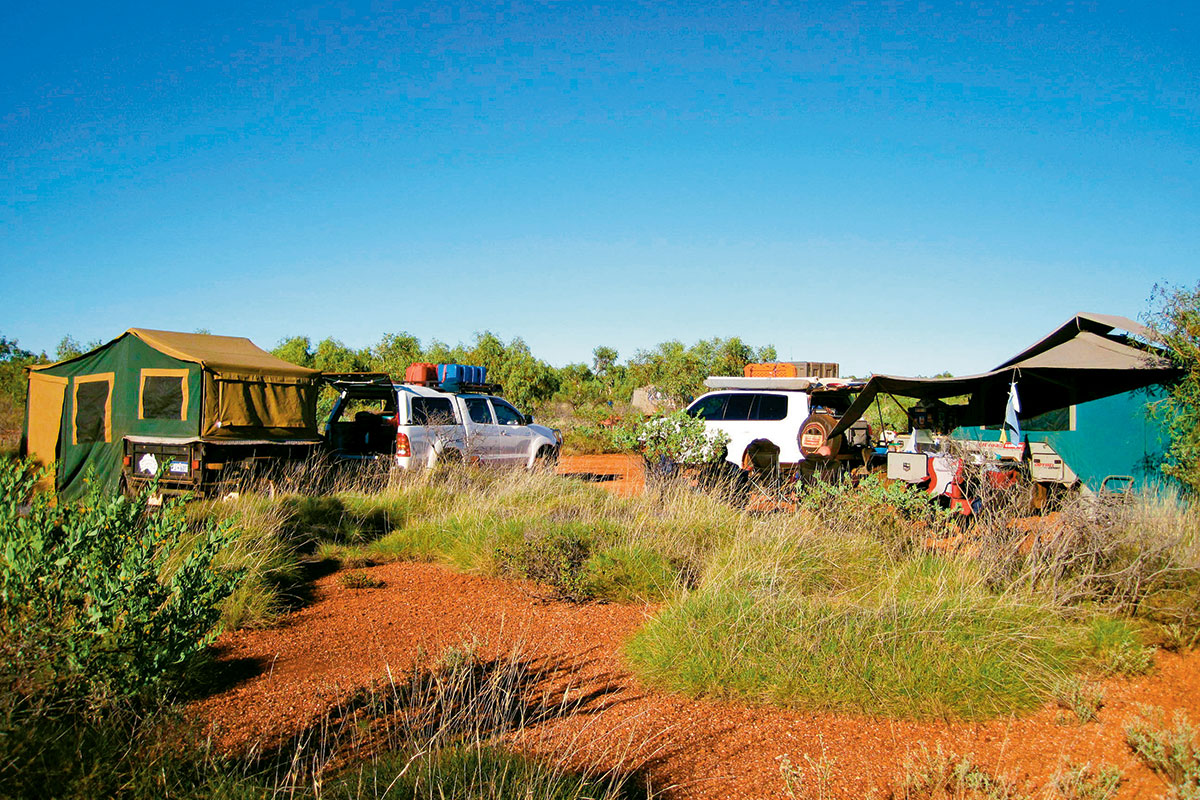 A campsite with two parked 4WD with tents