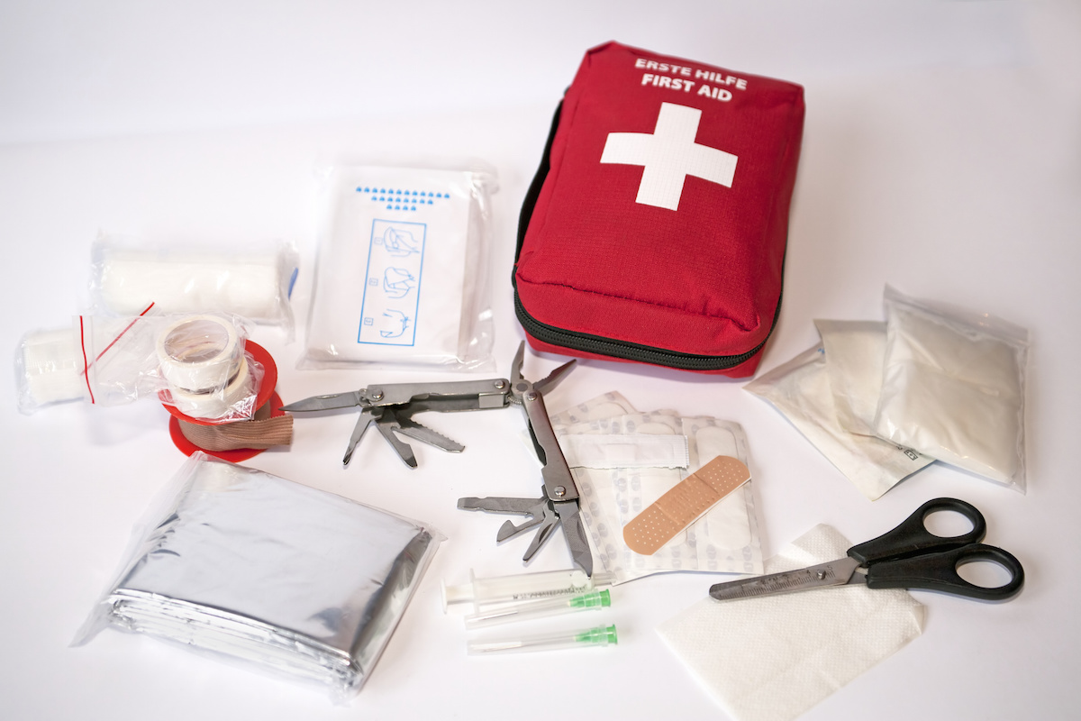 "Open first aid kit with bandages, scissors, ""triangle scarf"", syringe, plaster, knife, tools, gauze, etc"