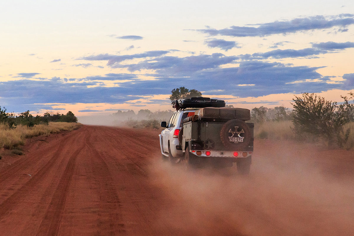 Car-driving-and-towing-a-camper-trailer-through-the-outback-at-the-Gibb-River-Road