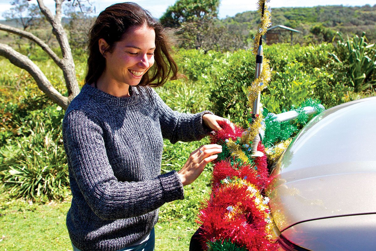 Woman-decorating-Christmas-tree-with-tinsel