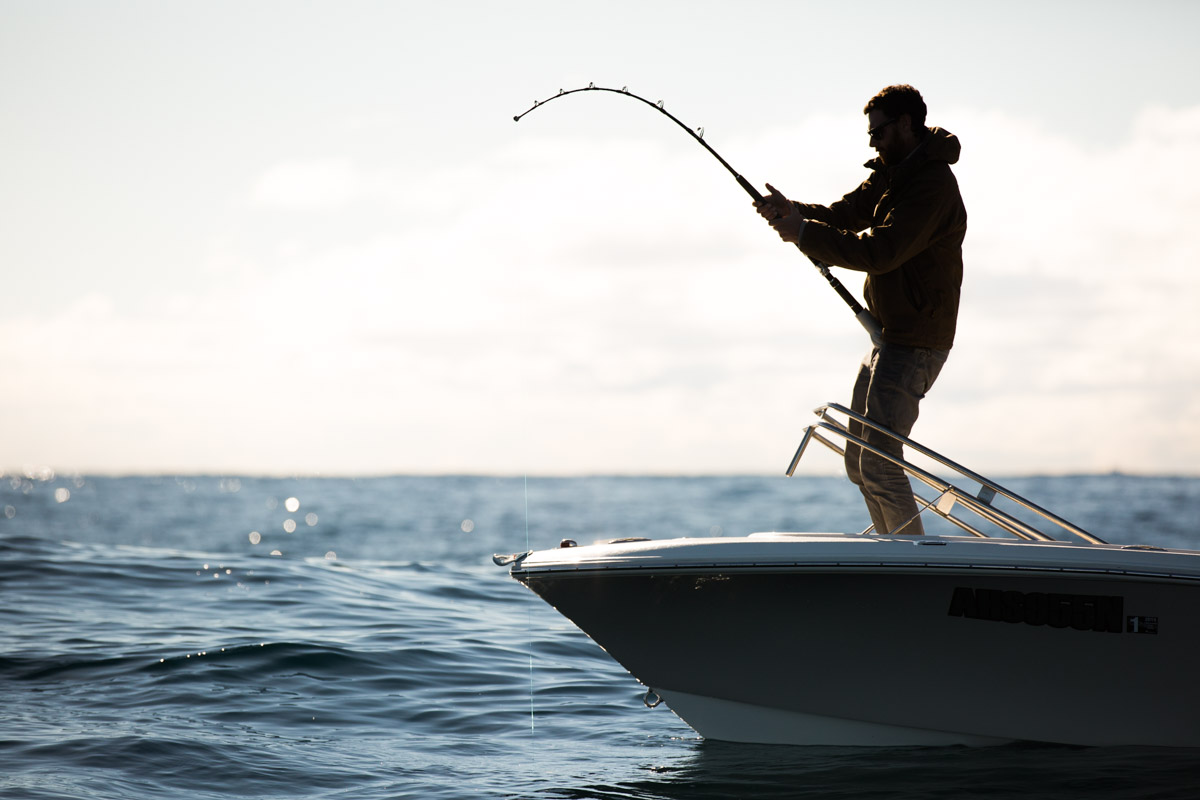 man on boat pulling in a fish