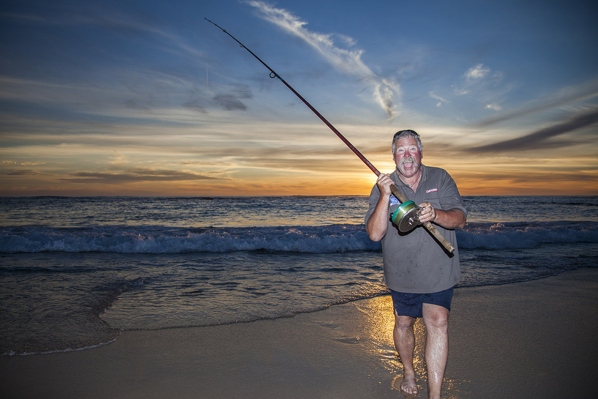 Man-fishing-at-the-beach-during-the-sunset
